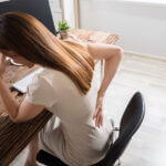 Businesswoman Having Back Pain At Workplace